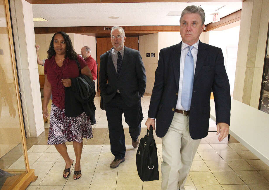 Monique Rathbun (from left), husband Marty and a witness, Mike Rinder, leave the courtroom for a break from a hearing regarding the suit against the Church of Scientology. Photo: Kin Man Hui / San Antonio Express-News / ©2013 San Antonio Express-News