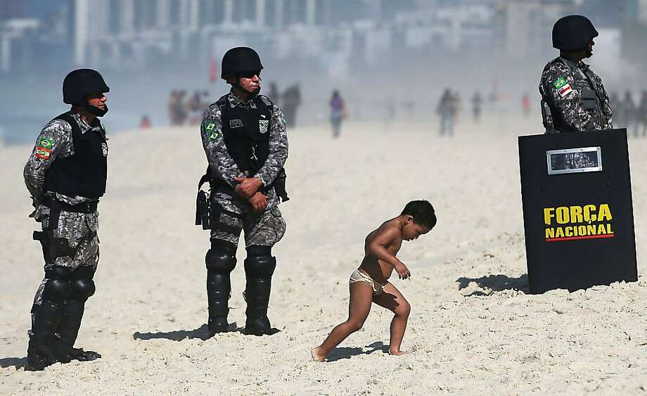 A boy walks past military police standing guard outside the seafront Windsor Barra hotel before the start of an auction of one of the world's biggest offshore oil finds on October 21, 2013 in Rio de Janeiro, Brazil. Brazil is auctioning its Libra offshore oilfield which holds between 8-12 billion barrels of oil and protesters are demonstrating outside the hotel against the participation of foreign oil companies. Photo: Mario Tama, Getty Images