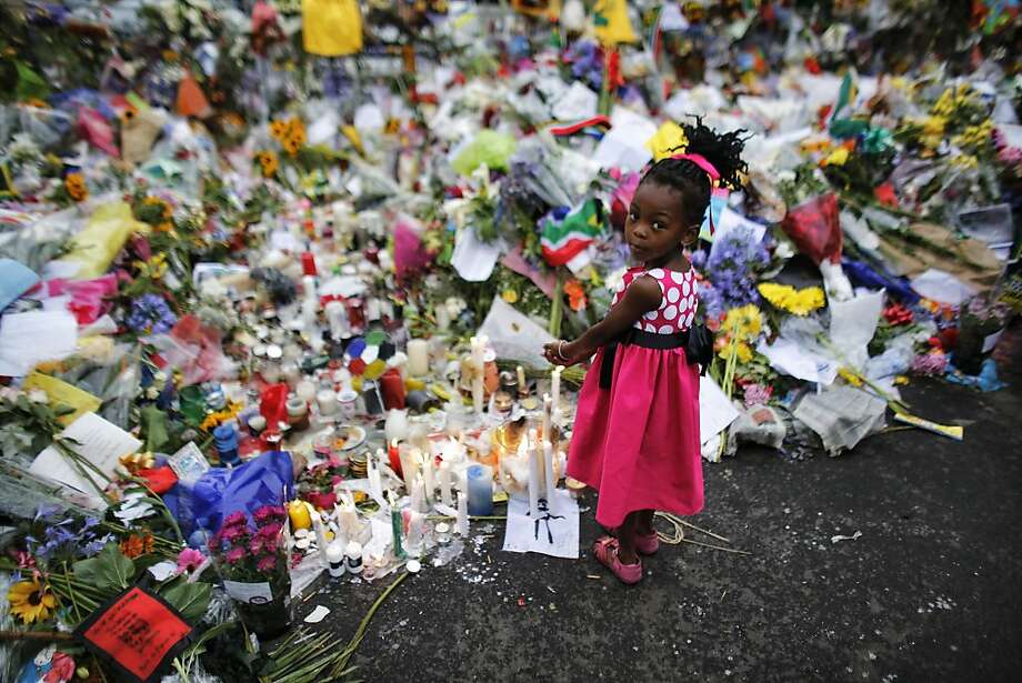 Four years old Bokamoso warms her hands over candles placed between flowers outside of the house of former South African President Nelson Mandela in Johannesburg, Monday, Dec. 9, 2013. Scores of heads of state and government and other foreign dignitaries, including royalty, are beginning to converge on South Africa as the final preparations for Tuesday's national memorial service for liberation struggle icon Nelson Mandela are put in place. Photo: Markus Schreiber, Associated Press