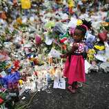 Four years old Bokamoso warms her hands over candles placed between flowers outside of the house of former South African President Nelson Mandela in Johannesburg, Monday, Dec. 9, 2013. Scores of heads of state and government and other foreign dignitaries, including royalty, are beginning to converge on South Africa as the final preparations for Tuesday's national memorial service for liberation struggle icon Nelson Mandela are put in place.