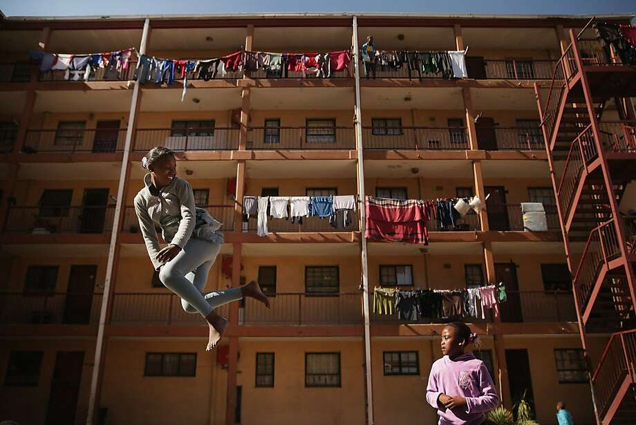 Phaphama Nxumalo (L), 12, and Natasha Mbatha, 9, members of the Alexandra Trampoline Club, practices in an alleyway between apartment blocks June 26, 2013 in Johannesburg, South Africa. A township with a wide spectrum of housing types, including shacks and contemporary homes, Alexandra is situated next to the wealthy suburb of Sandton, laying bare post-apartheid South Africa's vast gulf between wealth and poverty. Photo: Chip Somodevilla, Getty Images