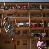 Phaphama Nxumalo (L), 12, and Natasha Mbatha, 9, members of the Alexandra Trampoline Club, practices in an alleyway between apartment blocks June 26, 2013 in Johannesburg, South Africa. A township with a wide spectrum of housing types, including shacks and contemporary homes, Alexandra is situated next to the wealthy suburb of Sandton, laying bare post-apartheid South Africa's vast gulf between wealth and poverty.