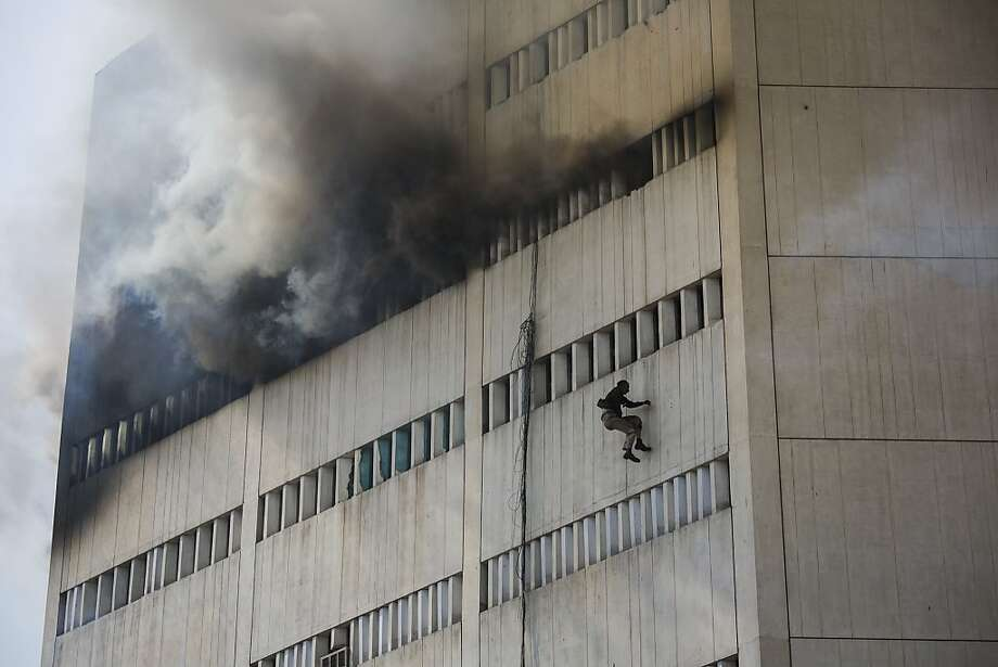 A man overcome by fumes falls out of a window as a fire burns at the Lahore Development Authority (LDA) Plaza on May 09, 2013 in Lahore, Pakistan. Rescue work is underway at the site of the fire with fire trucks being used to extinguish the fire and helicopters used to rescue stranded victims from the roof of the building. Photo: Daniel Berehulak, Getty Images