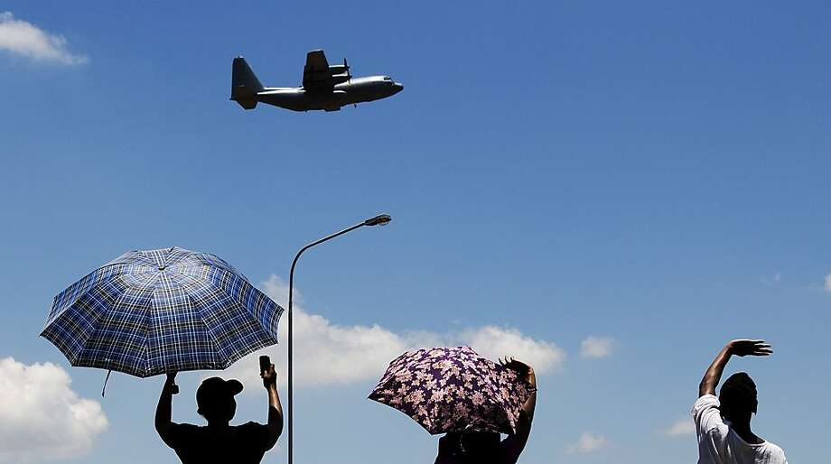 People wave at an aircraft carrying the casket of former South African President Nelson Mandela as it takes off from Waterkloof Air Base on the outskirts of Pretoria, South Africa, Saturday, Dec. 14, 2013.  On a final journey to his home village where he had wanted to spend his final days, the remains of Nelson Mandela were honored amid pomp and ceremony Saturday at an air base in South Africa's capital before being loaded onto a plane. Photo: Matt Dunham, Associated Press