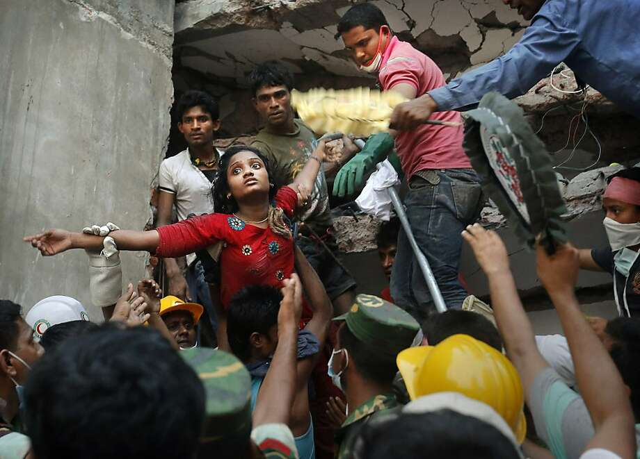 A Bangladeshi woman survivor is lifted out of the rubble by rescuers at the site of a building that collapsed Wednesday in Savar, near Dhaka, Bangladesh, Thursday, April 25, 2013. By Thursday, the death toll reached at least 194 people as rescuers continued to search for injured and missing, after a huge section of an eight-story building that housed several garment factories splintered into a pile of concrete. Photo: Kevin Frayer, Associated Press