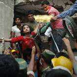 A Bangladeshi woman survivor is lifted out of the rubble by rescuers at the site of a building that collapsed Wednesday in Savar, near Dhaka, Bangladesh, Thursday, April 25, 2013. By Thursday, the death toll reached at least 194 people as rescuers continued to search for injured and missing, after a huge section of an eight-story building that housed several garment factories splintered into a pile of concrete.