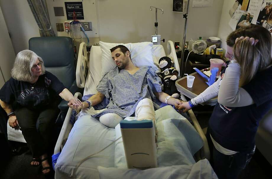 In this Thursday, May 9, 2013 photo, Marc Fucarile, center, holds hands with his mother, Maureen Fucarile, left, and his fiancee Jennifer Regan, right, in his room at Massachusetts General Hospital in Boston. Fucarile was only feet away from one of the bomb blasts Monday, April 15 near the finish line of the Boston Marathon that resulted in the loss of one leg, severe damage to the other, as well as burns, and a piece of shrapnel lodged in his heart. Photo: Steven Senne, Associated Press