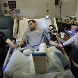 In this Thursday, May 9, 2013 photo, Marc Fucarile, center, holds hands with his mother, Maureen Fucarile, left, and his fiancee Jennifer Regan, right, in his room at Massachusetts General Hospital in Boston. Fucarile was only feet away from one of the bomb blasts Monday, April 15 near the finish line of the Boston Marathon that resulted in the loss of one leg, severe damage to the other, as well as burns, and a piece of shrapnel lodged in his heart.