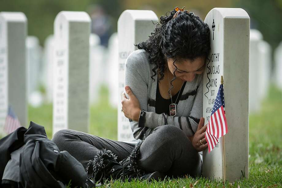 Thania Sayne of Effingham, Ill., leans on the headstone at the grave of her husband, Army Sgt. Timothy D. Sayne, during the playing of taps at a nearby burial service at Arlington National Cemetery, in Arlington, Va., Wednesday, Oct. 16, 2013, a day before what would have been their third wedding anniversary.  Sayne, was 4 months pregnant with their second son, Douglas, when her husband was killed on Sept. 18, 2011, in the Kandahar province of Afghanistan. Photo: Manuel Balce Ceneta, Associated Press