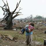 A woman carries her child through a field near the collapsed Plaza Towers Elementary School in Moore, Okla., Monday, May 20, 2013, following a massive tornado.