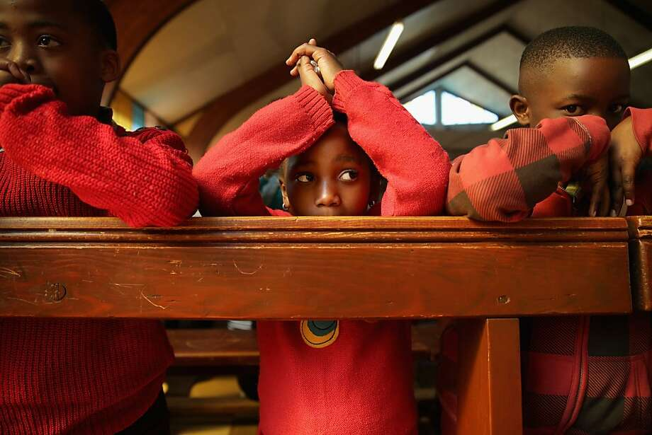 Children pray during a Catholic mass at the Regina Mundi Catholic Church in Soweto Township June 23, 2013 in Johannesburg, South Africa. The church played a central role in the anti-apartheid struggle, opening its doors to shelter to activists. During the June 16, 1976 student uprisings, protesting students fled to Regina Mundi from Orlando Stadium to escape police, who followed the students into the church, firing live ammunition and damaging the marble altar and crucifix. Photo: Chip Somodevilla, Getty Images
