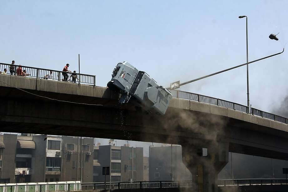 A police vehicle is pushed off of the 6th of October bridge by protesters close to the largest sit-in by supporters of ousted Islamist President Mohammed Morsi in the eastern Nasr City district of Cairo, Egypt, Wednesday, Aug. 14, 2013. Photo: Aly Hazzaa, Associated Press