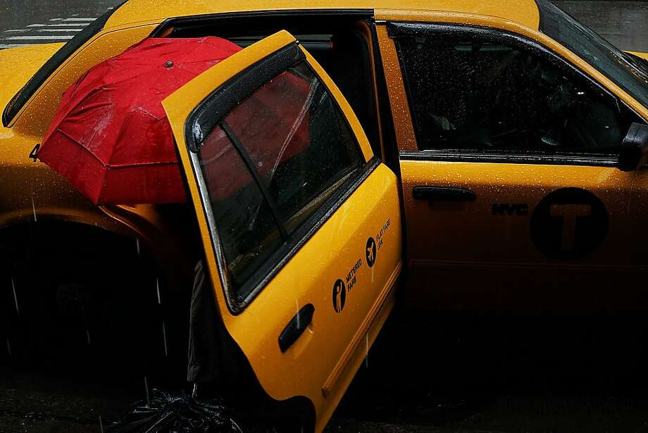 A woman exits a cab with an umbrella during a rain storm on May 8, 2013 in New York City. After experiencing an unusually dry spring in recent weeks, New York was hit with heavy rain Wednesday that resulted in numerous flash floods and heavy downpours. Photo: Spencer Platt, Getty Images