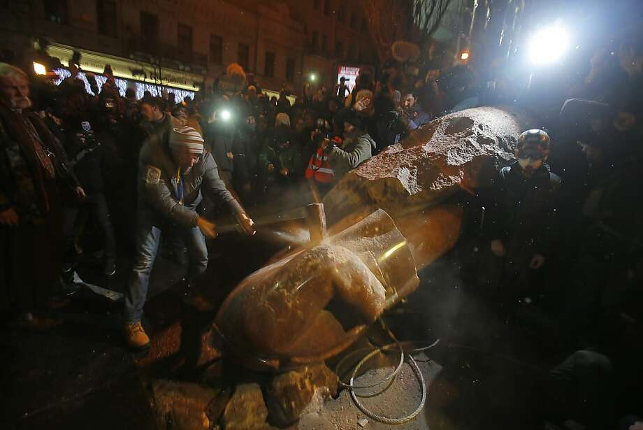 An anti-government protester smashes the statue of Vladimir Lenin with a sledgehammer in Kiev, Ukraine, Sunday, Dec. 8, 2013. Anti-government protesters have toppled the state of Bolshevik leader Vladimir Lenin in central Kiev amid huge protests gripping Ukraine. The chaotic protest further raised tensions in the Ukrainian capital. Photo: Sergei Grits, Associated Press