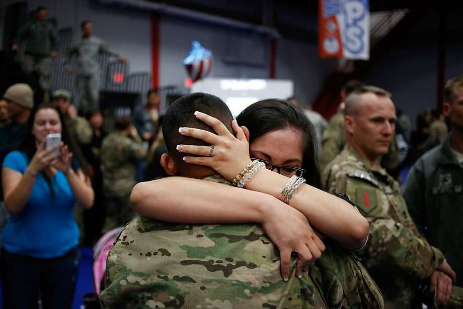Marlene Aceves embraces her husband Spc. Matthew Aceves of the U.S. Army's 3rd Brigade Combat Team, 1st Infantry Division, following a homecoming ceremony in the Natcher Physical Fitness Center on Fort Knox in the early morning hours of Wednesday, November 20, 2013 in Fort Knox, Ky. The 250 soldiers returned to Fort Knox after a nine-month combat deployment working alongside Afghan military and police forces in Afghanistan's Zabul Province. Photo: Luke Sharrett, Getty Images