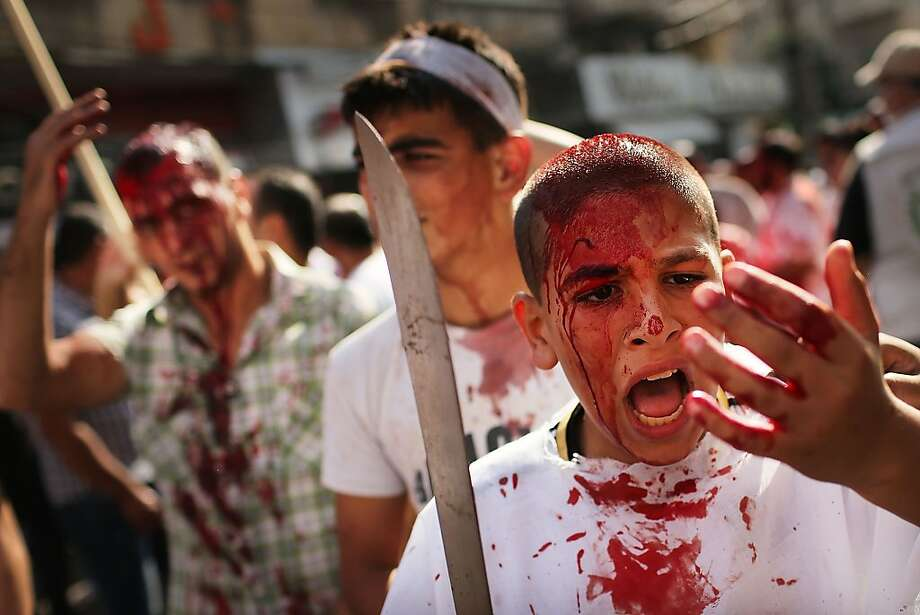 """Shiite Muslims bleed as they gash their foreheads with swords and beat themselves during a ceremony marking Ashura in Nabatiyeh, southern Lebanon on November 14, 2013 in Nabatieh, Lebanon. Shiite Muslims observe Ashura, day of mourning which means """"tenth"""" in Arabic, through mourning rituals such as reenactments of the martyrdom and self-flagellation. Most observers wear black and march through the streets chanting and hitting themselves in the chest and some still make small gashes to their heads to ritually punish their bodies. As the war in neighboring Syria drags on for a third year, Lebanon, a country of only 4 million people, is now home to the largest number of Syrian refugees who have fled the conflict. The situation is beginning to put huge social and political strains on Lebanon as there is currently no end in sight to the war in Syria. Photo: Spencer Platt, Getty Images"""