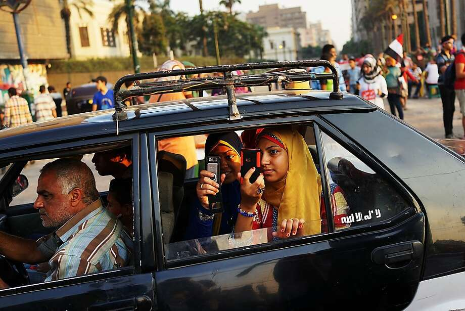 A family drives by Tahrir Square, the day after former Egyptian President Mohammed Morsi, the country's first democratically elected president, was ousted from power on July 4, 2013 in Cairo, Egypt. Adly Mansour, chief justice of the Supreme Constitutional Court, was sworn in as the interim head of state in ceremony in Cairo in the morning of July 4, the day after Morsi was placed under house arrest by the Egyptian military and the Constitution was suspended. Photo: Spencer Platt, Getty Images