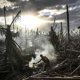 A man fans flames on a fire Tanauan on November 19, 2013 in Leyte, Philippines. Typhoon Haiyan which ripped through Philippines over a week ago has been described as on of the most powerful typhoons ever to hit land, leaving thousands dead and hundreds of thousands homeless. Countries all over the world have pledged relief aid to help support those affected by the typhoon however damage to the airport and roads have made moving the aid into the most affected areas very difficult. With dead bodies left out in the open air and very limited food, water and shelter, health concerns are growing.