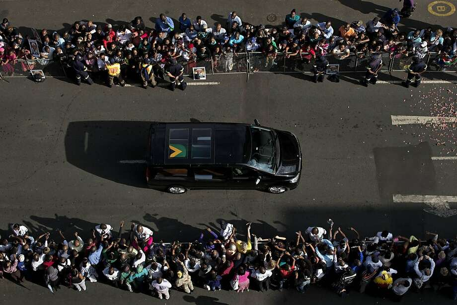 The funeral procession with the hearse carrying the body of Nelson Mandela drives towards the Union Buildings in Pretoria, South Africa, Thursday Dec. 12, 2013, where his body lies in state for the second day of three days of public viewing. Each morning his remains will be transported from the mortuary to the government buildings. Photo: Bernat Armangue, Associated Press