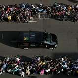 The funeral procession with the hearse carrying the body of Nelson Mandela drives towards the Union Buildings in Pretoria, South Africa, Thursday Dec. 12, 2013, where his body lies in state for the second day of three days of public viewing. Each morning his remains will be transported from the mortuary to the government buildings.