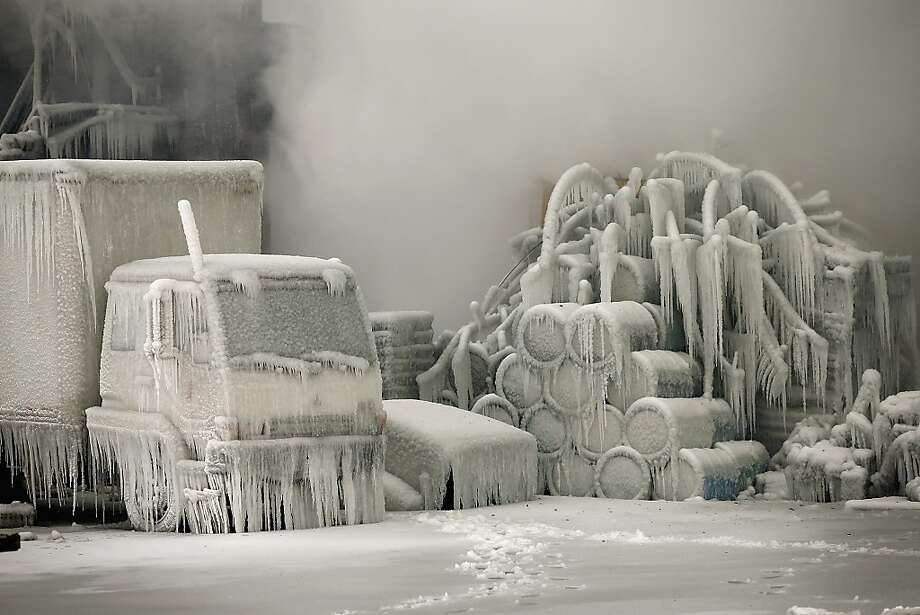 A truck is covered in ice as firefighters help to extinguish a massive blaze at a vacant warehouse on January 23, 2013 in Chicago, Illinois. More than 200 firefighters battled a five-alarm fire as temperatures were in the single digits. Photo: Scott Olson, Getty Images