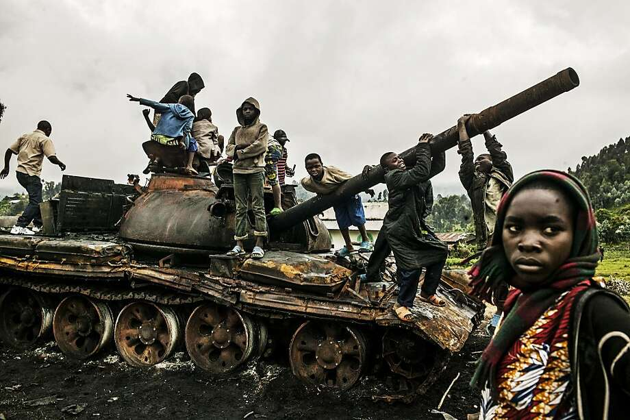 Children play on a destroyed M23 tank near Kibumba, north of Goma, Democratic Republic of Congo, Oct. 29, 2013. A feared rebel group in the Democratic Republic of Congo announced Tuesday that it was laying down its arms immediately, in a major development that held out hope of a new era of peace and stability in the violence-wracked region. Photo: Pete Muller, New York Times