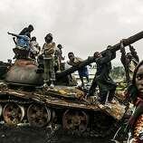 Children play on a destroyed M23 tank near Kibumba, north of Goma, Democratic Republic of Congo, Oct. 29, 2013. A feared rebel group in the Democratic Republic of Congo announced Tuesday that it was laying down its arms immediately, in a major development that held out hope of a new era of peace and stability in the violence-wracked region.