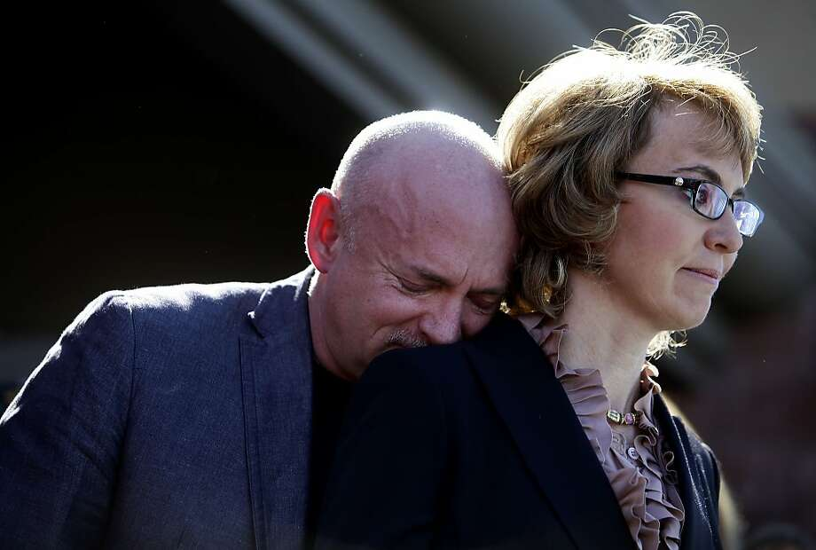 Mark Kelly leans his head on the shoulder of his wife and former Congresswoman Gabby Giffords as they attend a news conference asking Congress and the Senate to provide stricter gun control in the United States on March 6, 2013 in Tucson, Arizona. Giffords and Kelly were joined by survivors of the Tucson shooting as they spoke outside the Safeway grocery store where the shooting happened two years ago where six people were killed. Photo: Joshua Lott, Getty Images