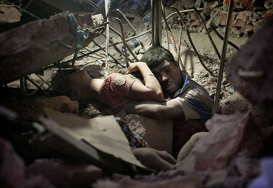 A Bangladeshi man holds on to a woman, both victims of a building collapse, in the debris of Rana Plaza garment factory in Savar near Dhaka, Bangladesh, April 25, 2013. The collapse of Rana Plaza in Dhaka that killed 1,129 people. Photo: Suman Paul, Associated Press