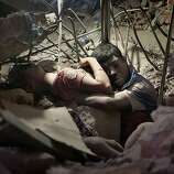 A Bangladeshi man holds on to a woman, both victims of a building collapse, in the debris of Rana Plaza garment factory in Savar near Dhaka, Bangladesh, April 25, 2013. The collapse of Rana Plaza in Dhaka that killed 1,129 people.