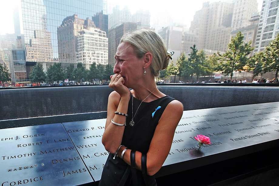 Carrie Bergonia of Pennsylvania looks over the name of her fiance, firefighter Joseph Ogren at the 9/11 Memorial during ceremonies for the twelfth anniversary of the terrorist attacks on lower Manhattan at the World Trade Center site on September 11, 2013 in New York City. The nation is commemorating the anniversary of the 2001 attacks which resulted in the deaths of nearly 3,000 people after two hijacked planes crashed into the World Trade Center, one into the Pentagon in Arlington, Virginia and one crash landed in Shanksville, Pennsylvania. Following the attacks in New York, the former location of the Twin Towers has been turned into the National September 11 Memorial & Museum. Photo: Pool, Getty Images