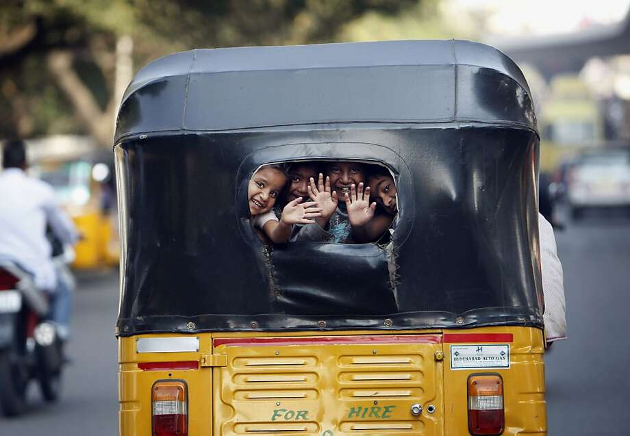 Indian children wave at commuters as they look out from the back window of an auto rickshaw in Hyderabad, India, Friday, Dec. 20, 2013. Motor rickshaws or auto rickshaws as they are popularly called in India, are used as an inexpensive means of transport. (AP Photo/Mahesh Kumar A.) Photo: Mahesh Kumar A., Associated Press