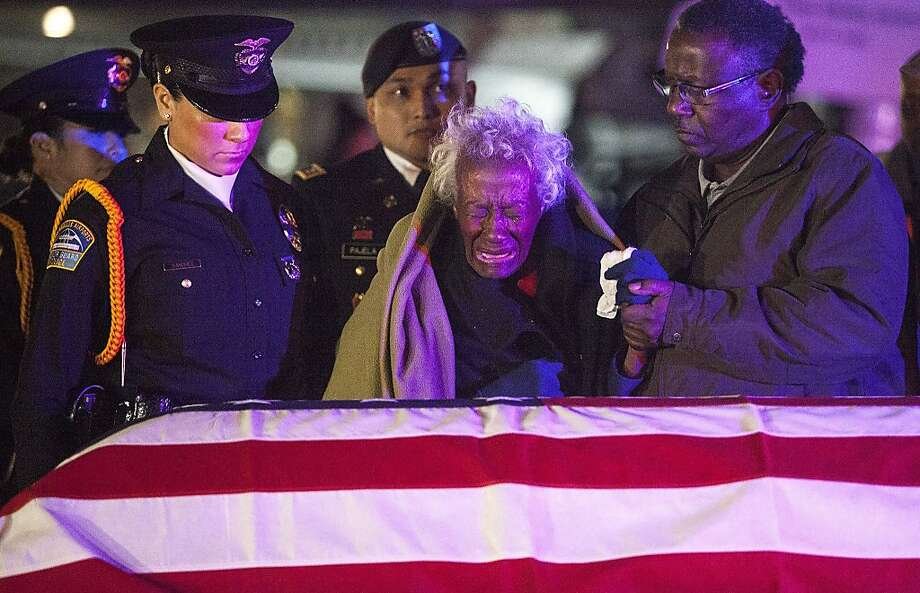 Clara Gantt, the 94-year-old widow of U.S. Army Sgt. Joseph Gantt, weeps in front of her her husband's casket after it is lowered from the plane on Friday, Dec. 20, 2013, at Los Angeles International Airport in El Segundo, Calif. Sgt. Gantt was captured in the Korean War and was missing for more than 63 years before his remains were recently identified. (Pool photo by Andrew Renneisen/Los Angeles Times/MCT) Photo: Andrew Renneisen, McClatchy-Tribune News Service