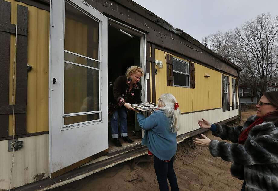"Rebuild Lyons board members Cathleen ""Chrystal"" Decoster, center, and pastor Emily Fleming, right, help local salon owner Jenna Brink retrieve an old photo album during a visit to her damaged home in a low-lying trailer park that was wrecked in floods the previous September, in Lyons, Colo., Friday, Dec. 20, 2013. Decoster and Fleming, with the Lyons Community Foundation and the Lyons Community Church's Community Basic Needs and Emergency Fund, distributed more than $950,000 to 280 people who submitted applications asking for help. (AP Photo/Brennan Linsley) Photo: Brennan Linsley, Associated Press"