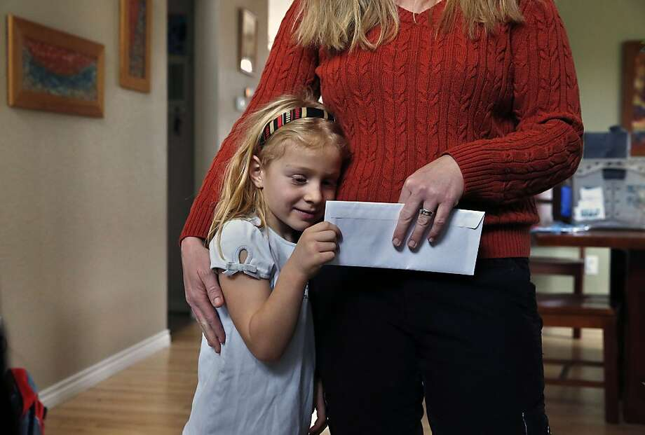 Heather Santesteban stands with her daughter Luci, 5, after receiving  a check from donated money on a day in which the Lyons Community Foundation  gave out checks totaling nearly $1 million to hundreds of locals who suffered the most as a result of September's massive flooding in Lyons, Colo., Friday Dec. 20, 2013. The Lyons Community Foundation and the Lyons Community Church's Community Basic Needs and Emergency Fund distributed more than $950,000 to 280 people who submitted applications asking for help. Most weren't notified in advance that they were selected to receive money. (AP Photo/Brennan Linsley) Photo: Brennan Linsley, Associated Press