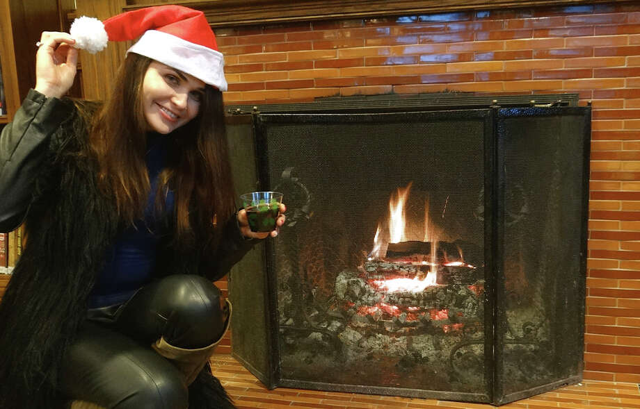 Anastasia Mihaleva enjoys the fireplace and the fun at Pequot Library's annual holiday party Friday evening. Photo: Mike Lauterborn / Fairfield Citizen contributed