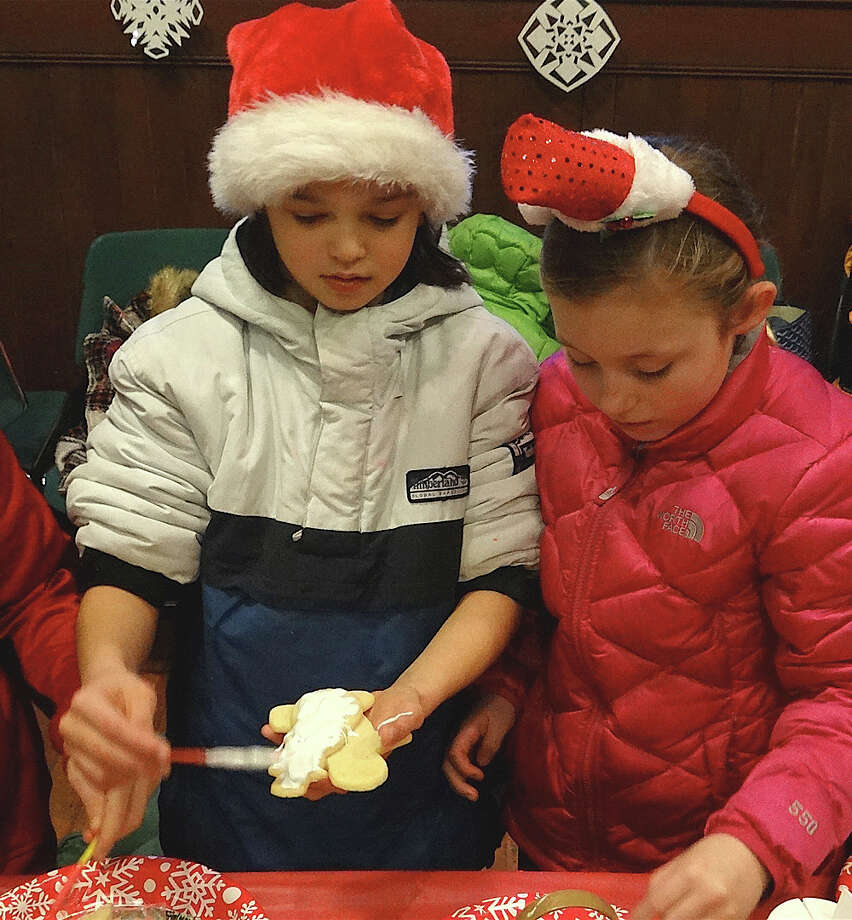 Southporters Ryan Voytas, 9, and Quinn Cunningham, 10, decorate Christmas cookies at the Pequot Library's holiday party Friday. Photo: Mike Lauterborn / Fairfield Citizen contributed