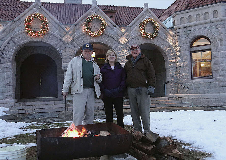 Don Lord, Harriet Hanley and Carl Poulsenn enjoy a bonfire on Pequot Library's snow-covered Great Lawn on Friday. Photo: Mike Lauterborn / Fairfield Citizen contributed