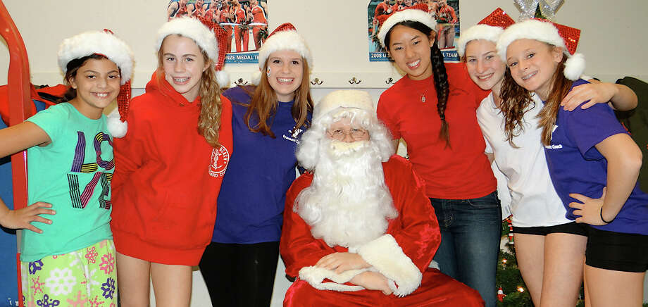 Santa Claus and helpers Friday at the Westport Weston Family Y included  Sonia Trinkle, 10; Abby Turner, 13; Maddy Mann, 18: Jessica Guo, 19; Emily Gruen, 14, and Aliza Dodge, 13. Photo: Mike Lauterborn / Westport News contributed