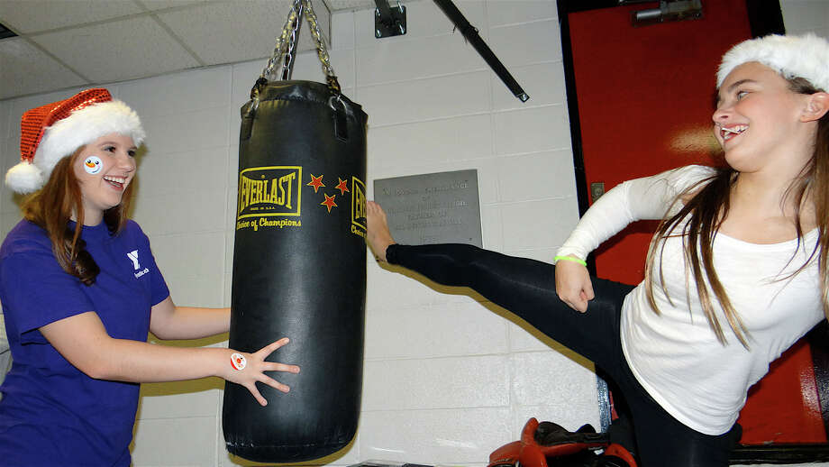Maddy Mann holds a boxing heavy bag for Bri Rotella as Bri lands a high kick at the Gymnastic Center of the Westport Weston Family Y's Pizza with Santa on Friday. Photo: Mike Lauterborn / Westport News contributed