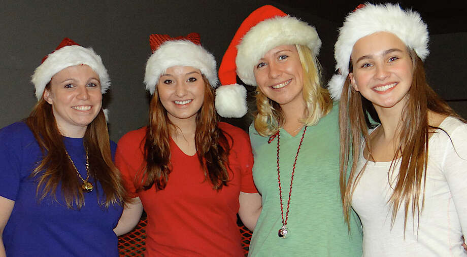 Santa's helpers Megan Willett, Laura Finell, Cara Loux and Bri Rotella staff the pizza and crafts table at the Westport Weston Family Y's Pizza with Santa event on Friday evening. Photo: Mike Lauterborn / Westport News contributed
