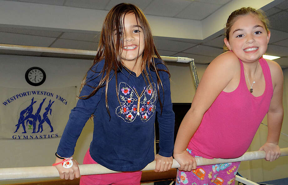 Westporters Alex Hackett, 6, and Morgan Carnahan, 8, balance on a high bar during the Westport Weston Family Y's Pizza with Santa event Friday. Photo: Mike Lauterborn / Westport News contributed