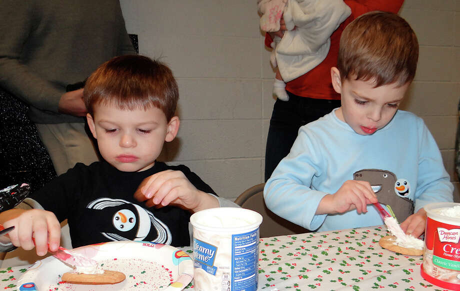 Leonardo Manzone, 3, of Southport, and Alan Mello, 3, of Westport, decorate cookies at the Westport Weston Family Y's Pizza with Santa event. Photo: Mike Lauterborn / Westport News contributed