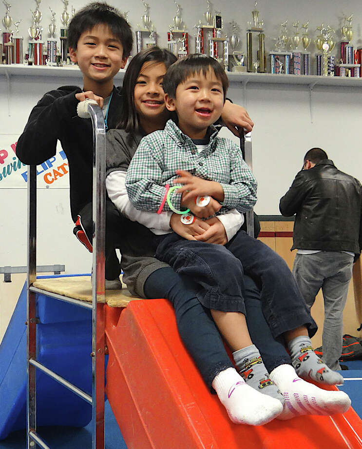 Siblings Danny, Caitlin and Tyler Chu, ages 10, 8 and 4, of Westport, pile onto a slide during the Pizza with Santa event at the Westport Weston Family Y. Photo: Mike Lauterborn / Westport News contributed