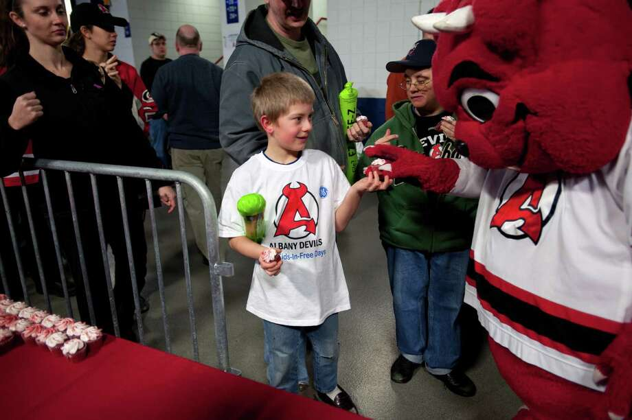 Devil Dawg gives a birthday cupcake to a fan at GE Kids in Free Day at the Albany Devils hockey game, Times Union Center, Albany. This year?s event will be held Saturday, Jan. 11,  at 5 p.m. during a game against the Manchester Monarchs. All children 12 and under receive free admission and the first 1,000 kids to arrive will receive a Devils t-shirt. (Photo by James DiBianco Jr.) Photo: James DiBianco / Copyright 2013 James DiBianco