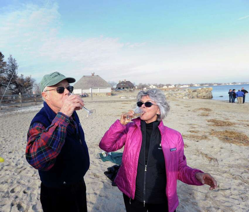 With the temperature reading 58 degrees on the first day of winter, the shortest day of the year, John Nelson, left, and Diana Frazier, both of Greenwich, celebrate the winter solstice and the holidays with champagne at Greenwich Point, Saturday, Dec. 21, 2013.