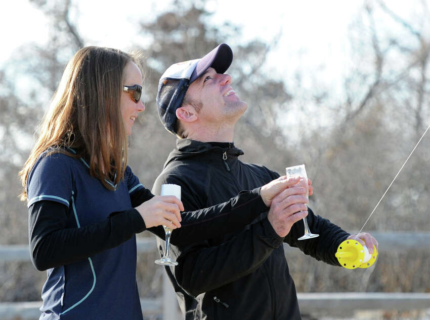 With the temperature reading 58 degrees on the first day of winter, the shortest day of the year, Mike Kautz, right, and Abby Nelson, a Greenwich native, hold glasses of champagne while flying a kite at Greenwich Point, Saturday, Dec. 21, 2013.