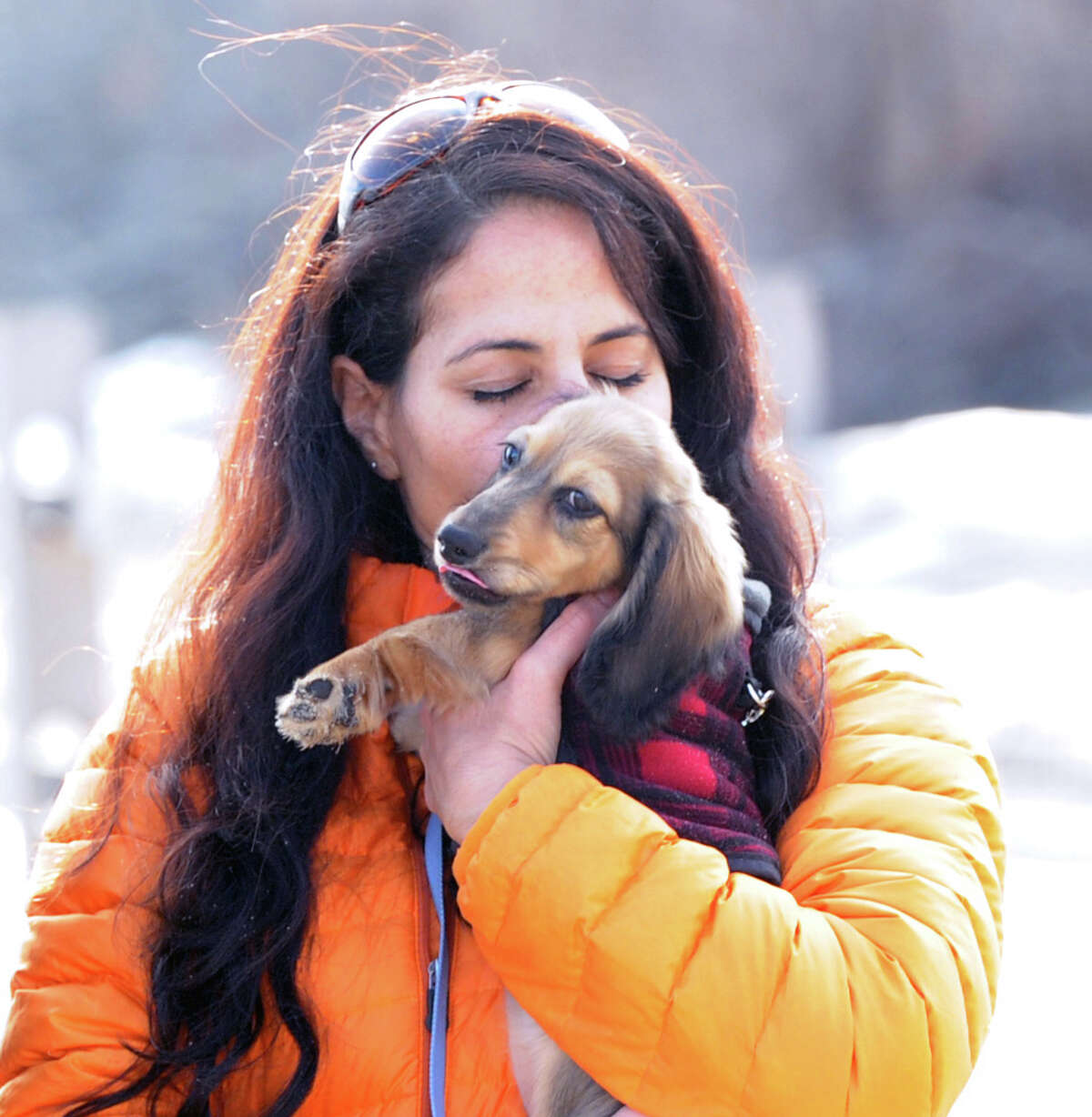 With the temperature reading 58 degrees on the first day of winter, the shortest day of the year, Maria Scrivan of Greenwich, nuzzles her nose against the ear of her Miniature long hair Dachshund, Toby, at Greenwich Point, Saturday, Dec. 21, 2013.