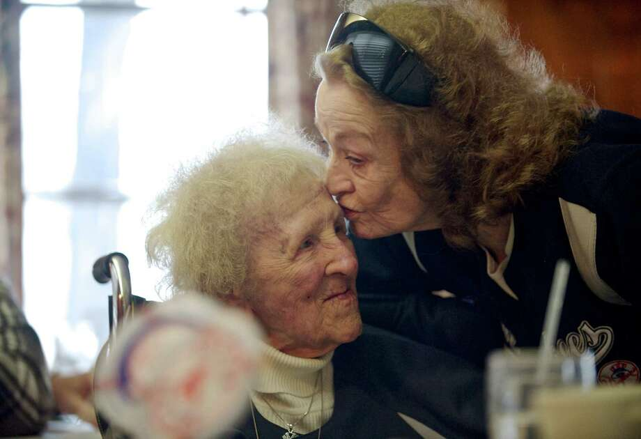 Dorothy Juliette, of Danbury, celebrates her 100th birthday, her birthdate is December, 27, 1913, with a baseball themed party at The Hearth Restaurant, in Brookfield Conn, on Saturday, December 21, 2013.  Fellow Yankee fan, Barbara Blake, of New Fairfield, leans in to give Dorothy a kiss during her birthday party. Photo: H John Voorhees III / The News-Times Freelance