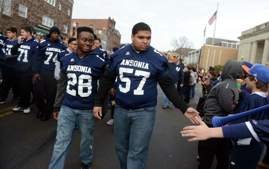 Ansonia High School football players Hugh Jackson (28) and Antone Mack (57) march down Main Street with the rest of the Chargers, and Ansonia Youth cheerleaders, AYC National Championship winners and runners-up, Saturday, Dec. 21, 2013 during a parade in their honor in downtown Ansonia, Conn. Photo: Autumn Driscoll / Connecticut Post